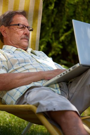 Healthy senior man is his elderly 70s sitting outdoor in garden at home and using laptop computer to browse internet. Stock Photo - 6438832