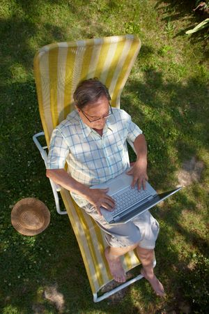 sinecure: Healthy senior man is his elderly 70s sitting outdoor in garden at home and using laptop computer to browse internet.