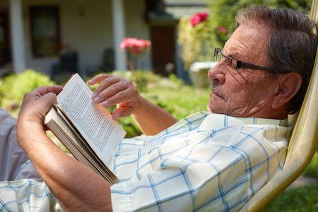 reyes magos: Hombre de senior aspecto saludable es su finales de los 70 sentado en el jard�n en el hogar y el libro de lectura, al aire libre.