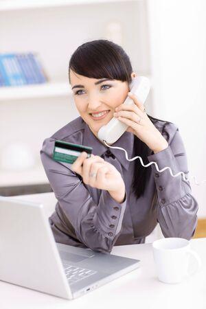 orden de compra: Sonriendo a las mujeres j�venes en su casa de compras en l�nea, con tarjeta de cr�dito en la mano y hablando por tel�fono. Foto de archivo