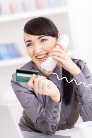 Smiling young women shopping online at home, holding credit card in hand and talking on phone. photo