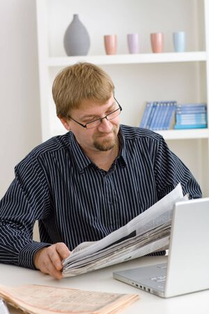 Man reading newspaper at home sitting at table with laptop. photo
