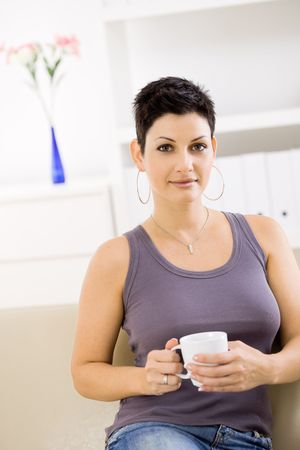 Young woman wearing jeans and tank top, sitting on couch at home, drinking coffee. photo