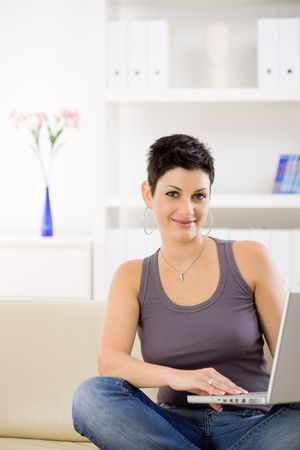 Young woman wearing jeans and tank top, sitting on couch at home, browsing internet on laptop computer, smiling. photo