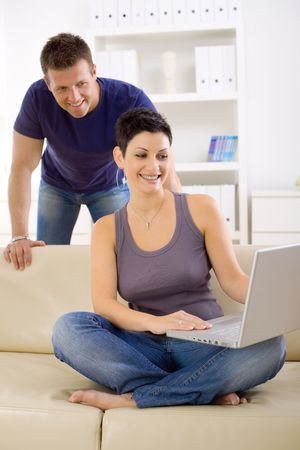 Couple using laptop computer at home together, looking at screen, smiling. photo