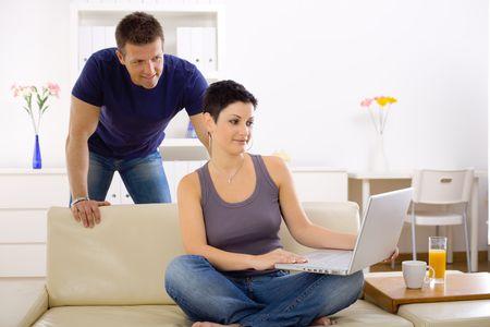BUEN VIVIR: Par utiliza equipo port�til en casa juntos, mirando la pantalla, sonriendo. Foto de archivo