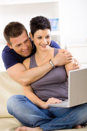 BUEN VIVIR: Pareja utiliza equipo port�til en casa juntos, hombre mujer abrazos, sonriendo.