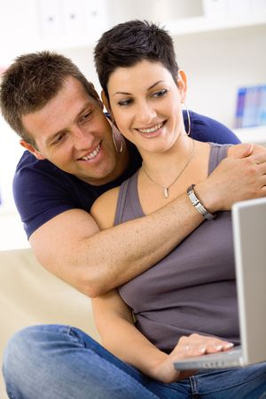 Couple using laptop computer at home together, man hugging woman, smiling. photo