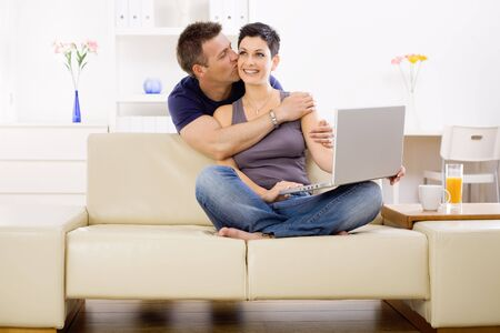 Couple using laptop computer at home together, man hugging and kissing woman, smiling. photo