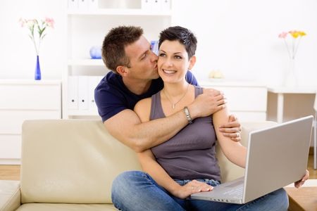 young couple hugging kissing: Couple using laptop computer at home together, man hugging and kissing woman, smiling.