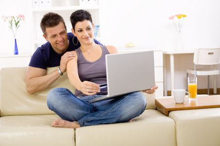 Couple using laptop computer at home together, looking at screen, smiling. Stock Photo - 6463483