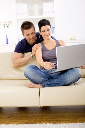 Couple using laptop computer at home together, looking at screen, smiling. Stock Photo - 6463399