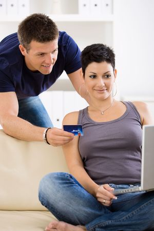 Happy young couple paying with credit card at home, smiling. Stock Photo - 6463515