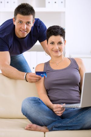 Happy young couple shopping online at home using laptop computer, looking at credit card, smiling. photo
