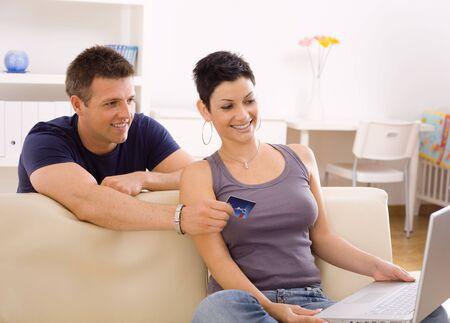 Purchase Order: Feliz pareja joven de compras en l�nea en casa utilizando el ordenador port�til, mirando de tarjeta de cr�dito, sonriendo.
