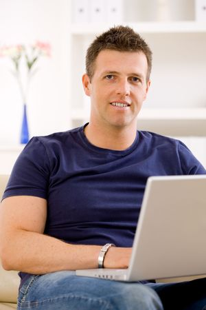 Man sitting on sofa at home and using laptop computer. Stock Photo - 6463449