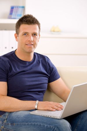 Man sitting on sofa at home and using laptop computer. Stock Photo - 6463480