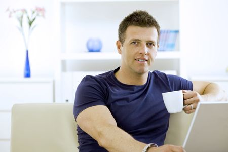 hombre tomando cafe: Relajado joven beber café en casa, sentado en el sofá. Foto de archivo