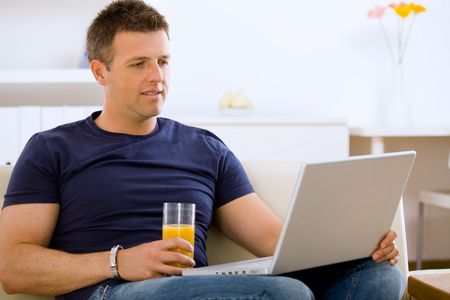Man sitting on sofa at home and using laptop computer. Stock Photo - 6463406