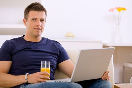 Man sitting on sofa at home and using laptop computer. Stock Photo - 6463451