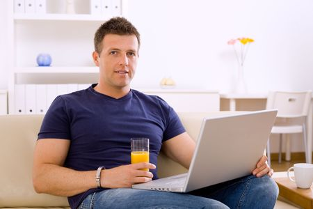 Young man sitting on sofa at home and using laptop computer.