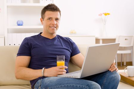 outworking: Young man sitting on sofa at home and using laptop computer.