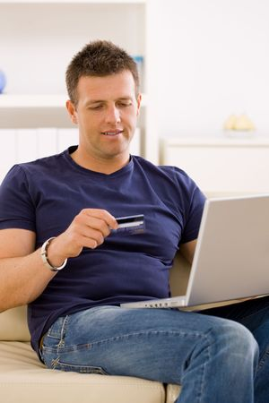 Young man shopping online at home using laptop computer, sitting on couch, looking at credit card. photo