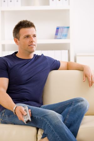 only 1 man: Man watching TV at home, sitting on beige couch, holding remote control in hand.