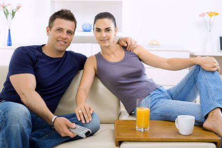 Young couple watching TV at home, sitting on beige couch, holding remote control in hand. photo