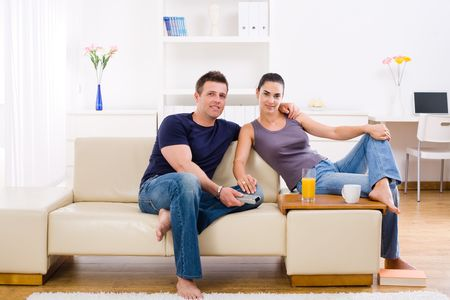 Happy young couple sitting on sofa at home, smiling. Stock Photo - 6463538