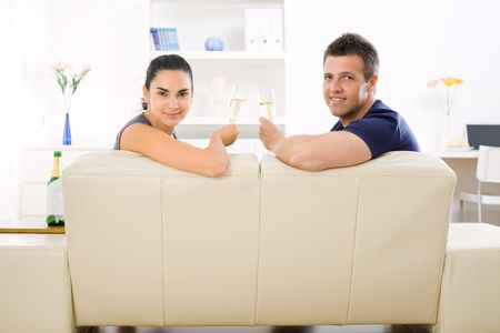 Love couple drinking champagne at home on sofa. Smiling and looking at camera. photo