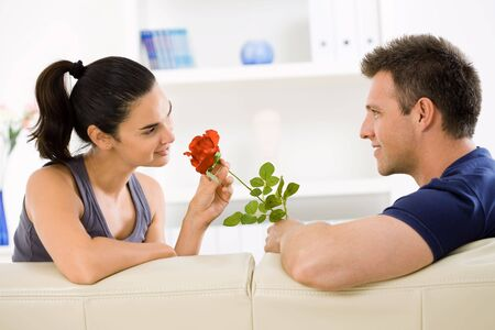 Romantic man giving red rose to woman for Valentines Day. photo