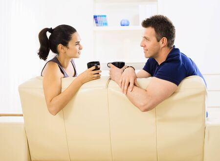 Young couple drinking coffee at home sitting on couch. Smiling and looking at each other. photo