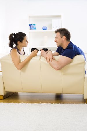 sipping: Young couple drinking coffee at home sitting on couch. Smiling and looking at each other. Stock Photo