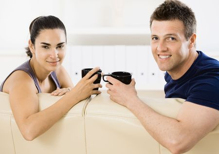 Young couple drinking coffee at home sitting on couch. Smiling and looking at camera. photo