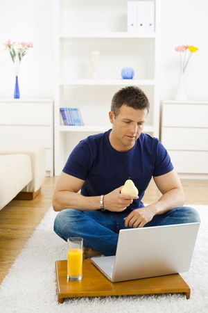 outworking: Casual young man working at home on his laptop, sitting on floor and holind pear in hand.