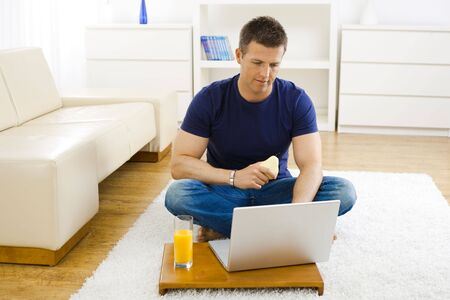 outworking: Casual young man using laptop computer at home, sitting at floor, holding pear in hand.