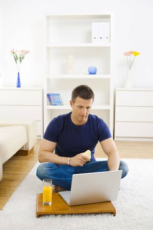 Casual young man working at home on his laptop, sitting on floor and holind pear in hand.