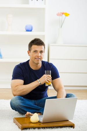 outworking: Casual young man working at home on his laptop computer, sitting on floor and drinking orange juice.