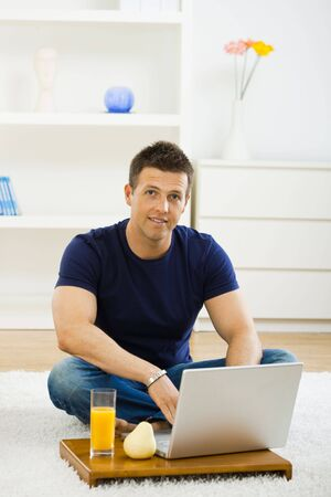 outworking: Casual young man working at home on his laptop, sitting on floor, smiling and looking at camera. Stock Photo