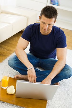 outworking: Casual young man working at home on his laptop computer, sitting on floor, looking at screen. High angle view. Stock Photo
