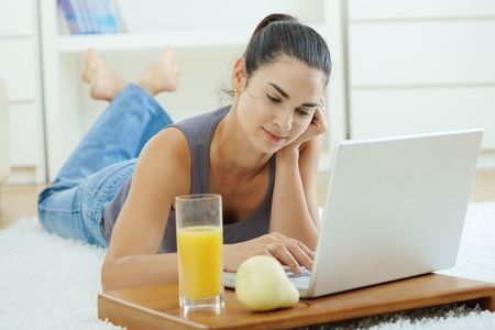 Happy woman lying on floor at home and working on laptop computer, smiling. Stock Photo - 6463534
