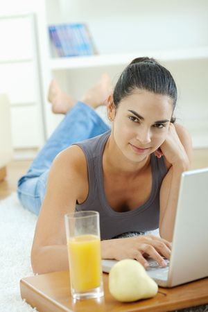 Happy woman lying on floor at home and working on laptop computer, smiling.
