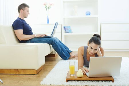 Young woman lying on floor at home using laptop computer. photo