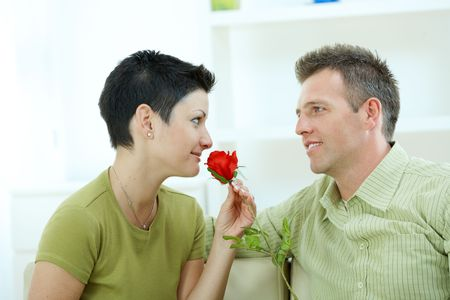 Romantic man giving red rose to woman at home, smiling. Stock Photo - 6463476