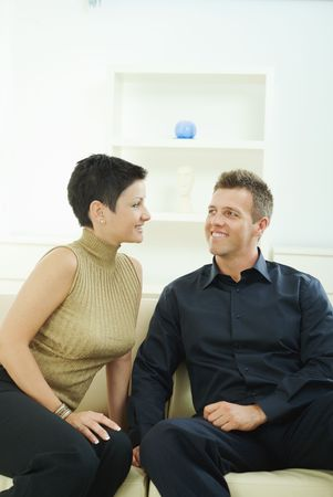 Happy young couple sitting together on sofa at home, looking at each other, smiling. photo