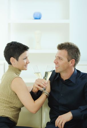 Love couple clinking champagne glasses at home on sofa. Smiling and looking at each other. photo