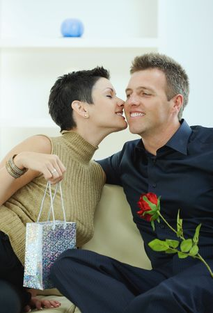 Love couple celebrating birthday, giving present and red rose, kissing. photo
