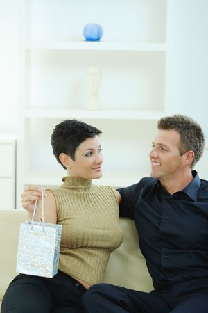 Love couple celebrating birthday, giving present, looking at each other, smiling. photo