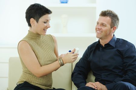 Man giving engagement ring to woman at home, smiling. photo